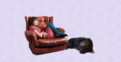 Persona en sofá, perro a su lado en el piso